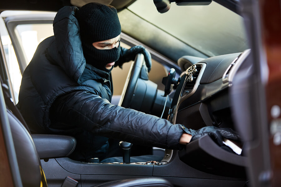 Thief-in-the-car-rummages-through-glove-compartment-for-garage-door-remote
