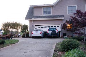 damaged-white-garage-door-2-cars-in-front