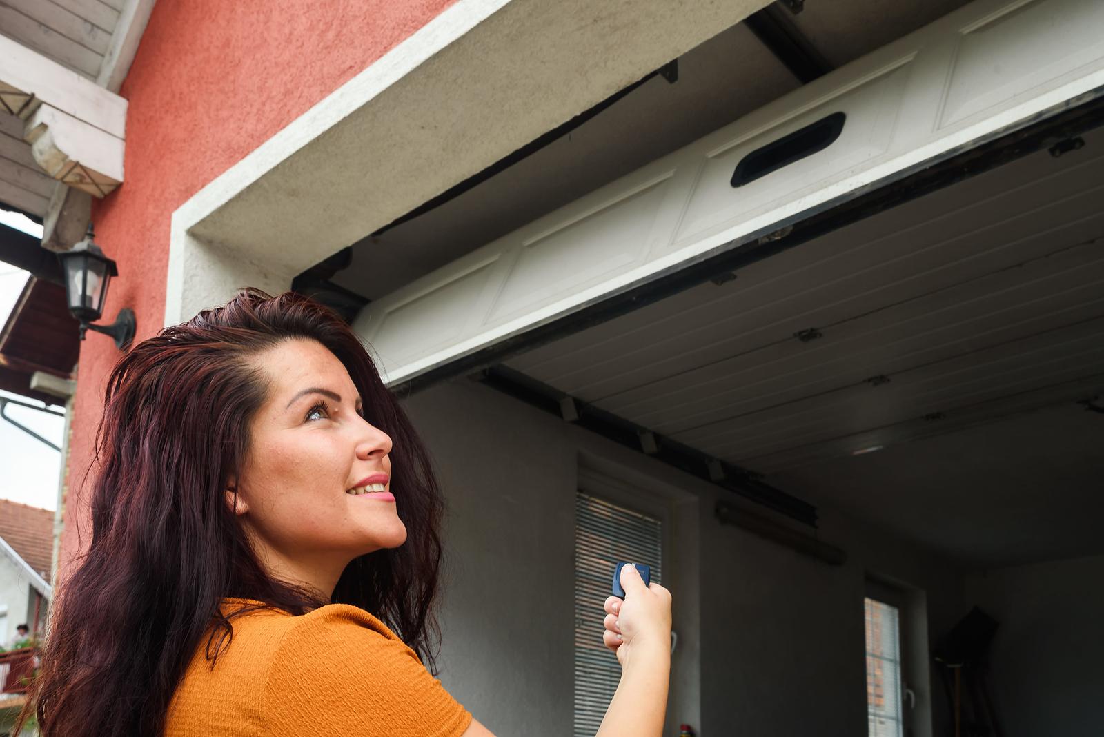 woman-using-garage-door-opener-outside-of-garage-door
