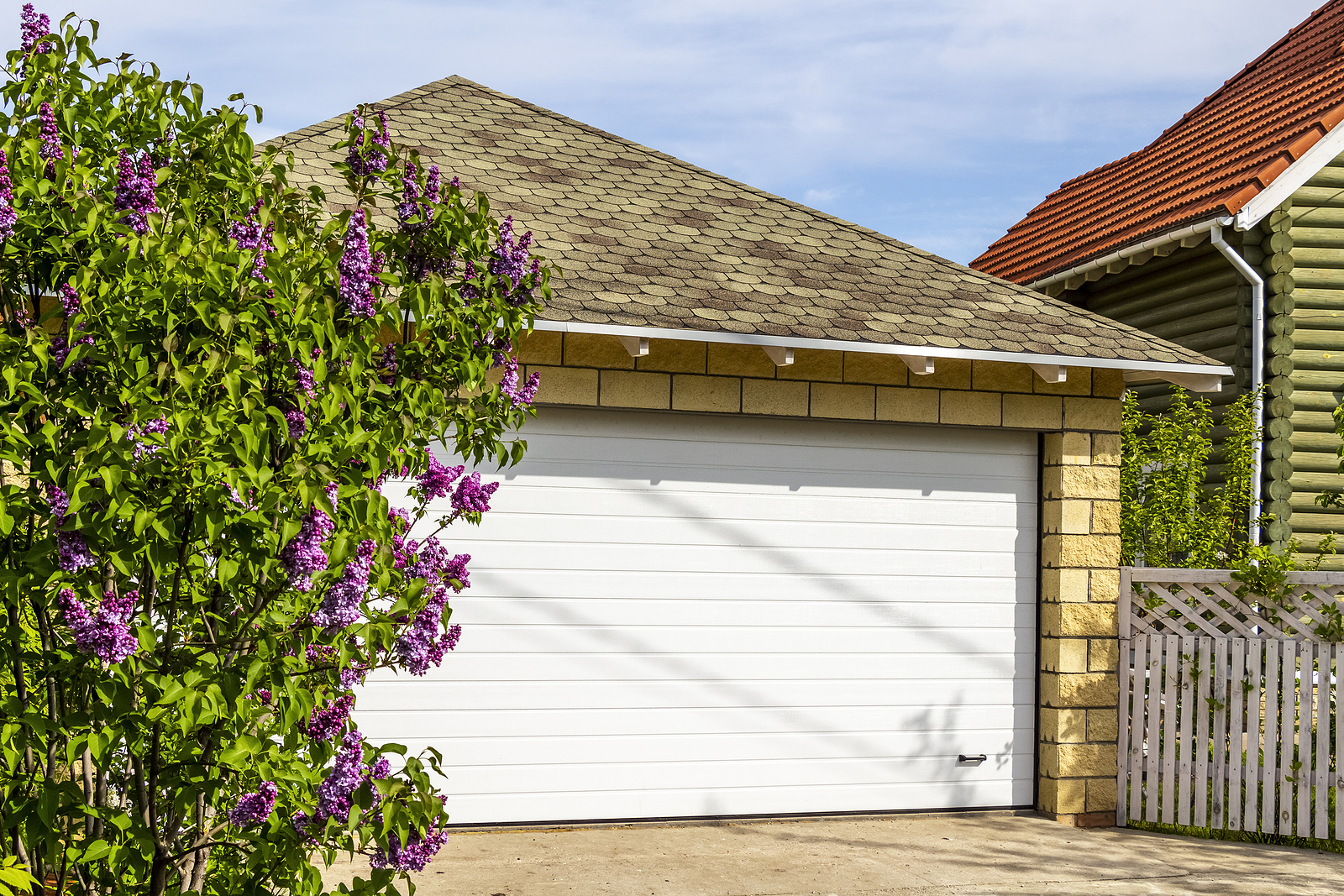White-Garage-Doors-of-a-Private-House-and-Nearby-Lilac-Bushes