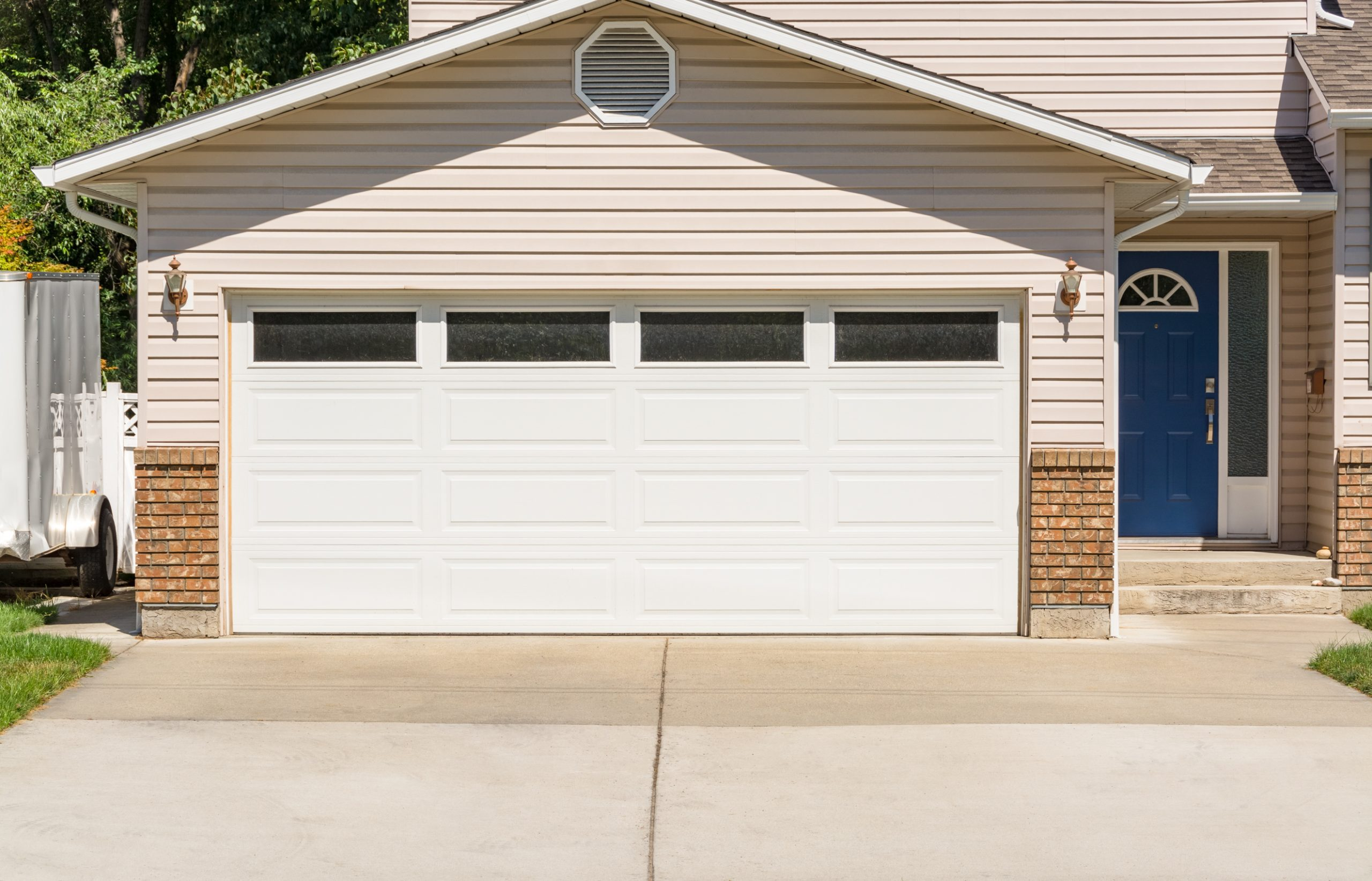 Wide-Garage-Door-Of-Residential-House-with-Concrete-Driveway-in-Front-