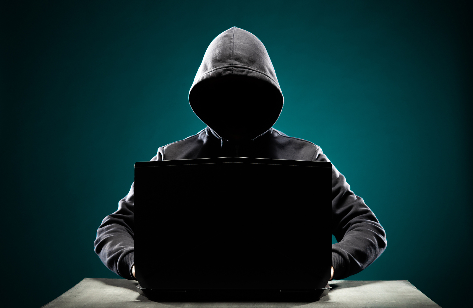 Computer-Hacker-In-Hoodie-Sweater-with-Obscured-Face-Using-Laptop