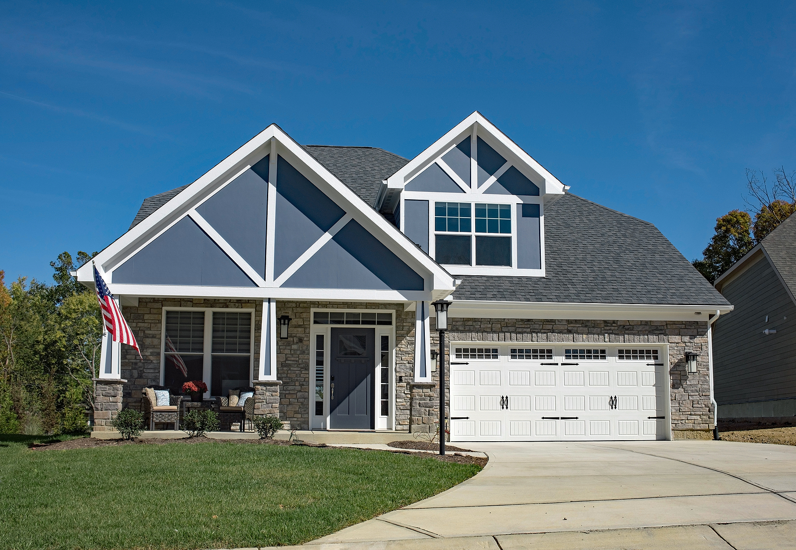 New-American-Stone-Home-with-Blue-Decorative-Gables-and-White-Decorated-Garage-Door